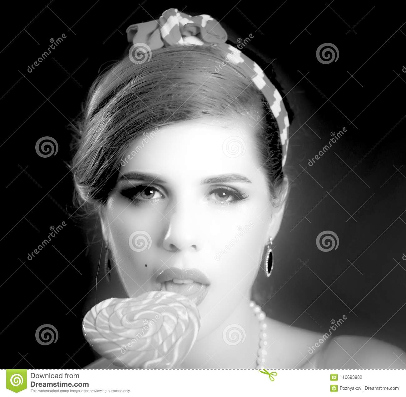 Woman eating lollipops. Girl in pin-up style hold striped candy.