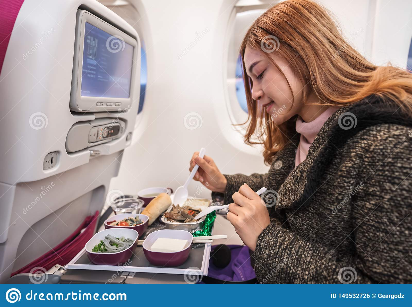 Woman eating meal on commercial airplane in flight time