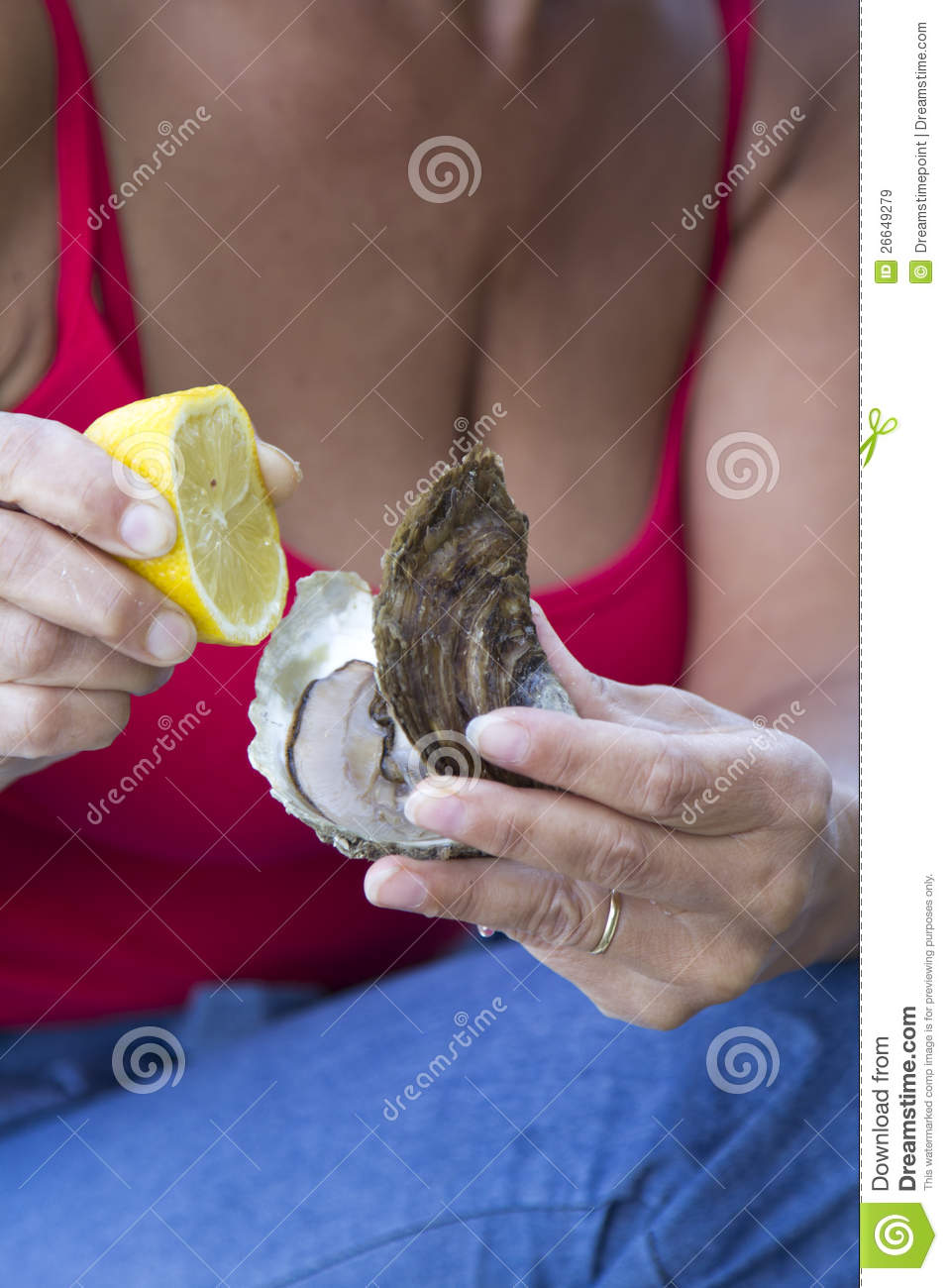 Woman preparing to eat delicious raw oyster with fresh lemon.