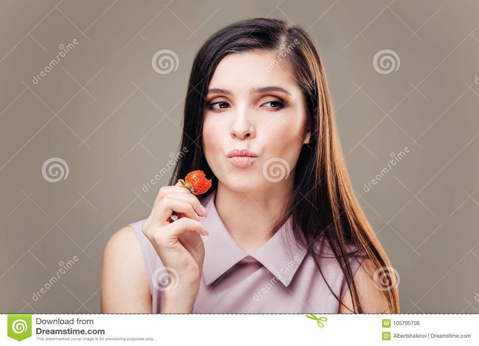 1ba8db49bd54e Woman eating strawberries. Healthy happy smiling woman eating strawberry.  Gorgeous smile on mixed Caucasian Asian female model.