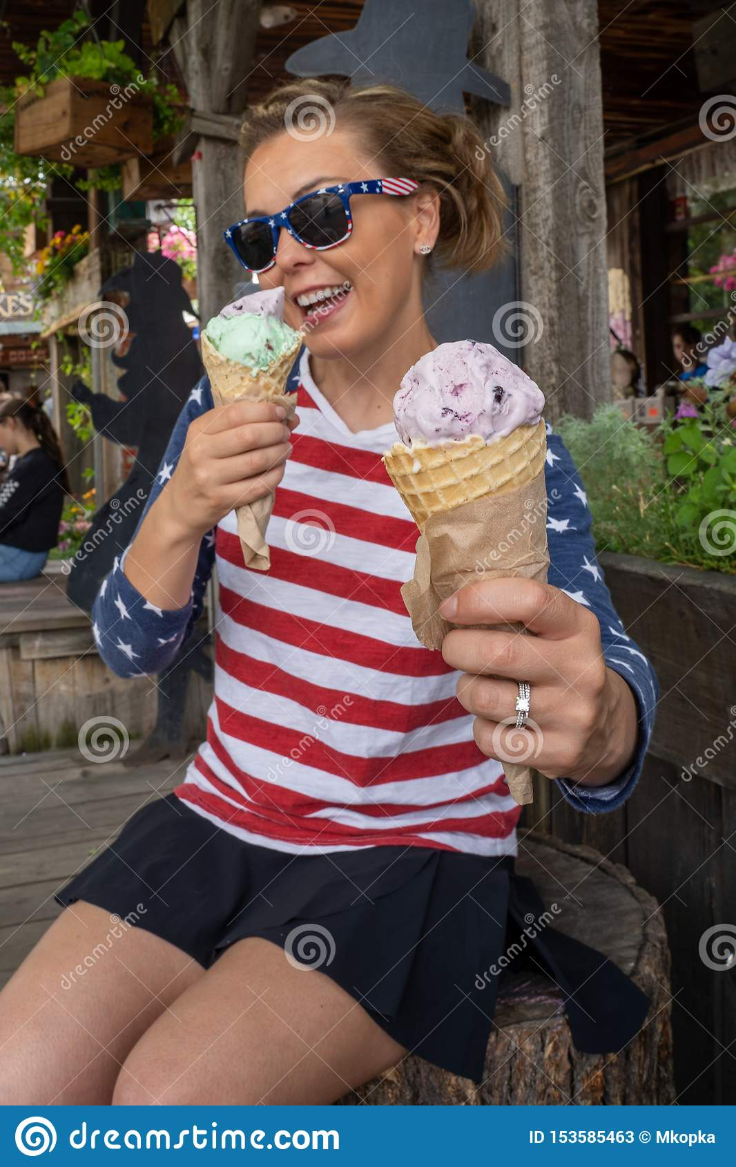 Woman eats two waffle ice cream cones, sitting down, smiling, wearing patriotic american USA clothing and sunglasses