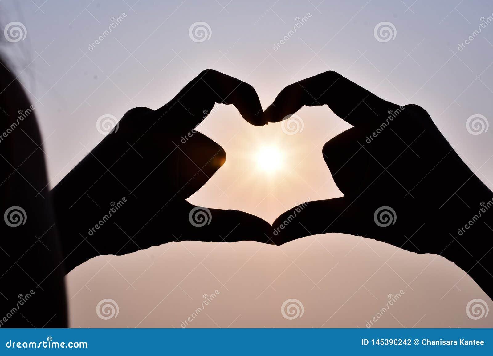 Woman&en x27; s-handen - gjorde en hjärtaform, med solen som ner, i hemlighet går i mitt och himlen i aftonen