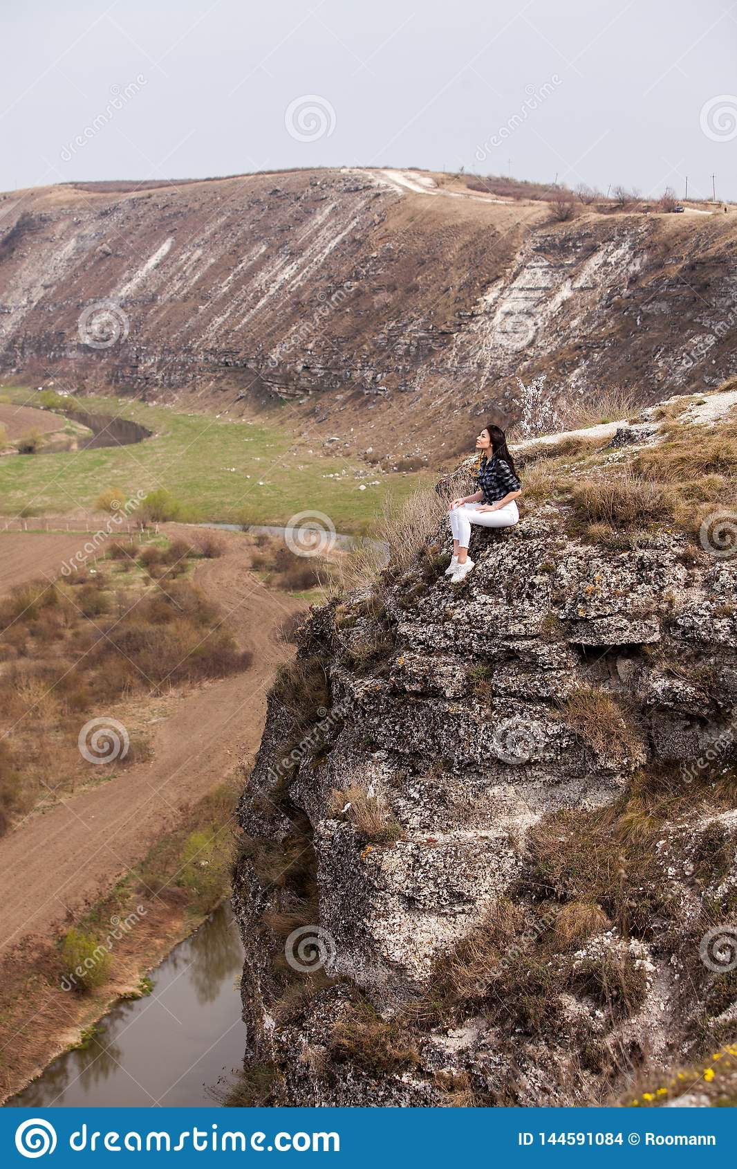 A young traveler girl sit on the top of valley. Young girl love wild life, travel, freedom.