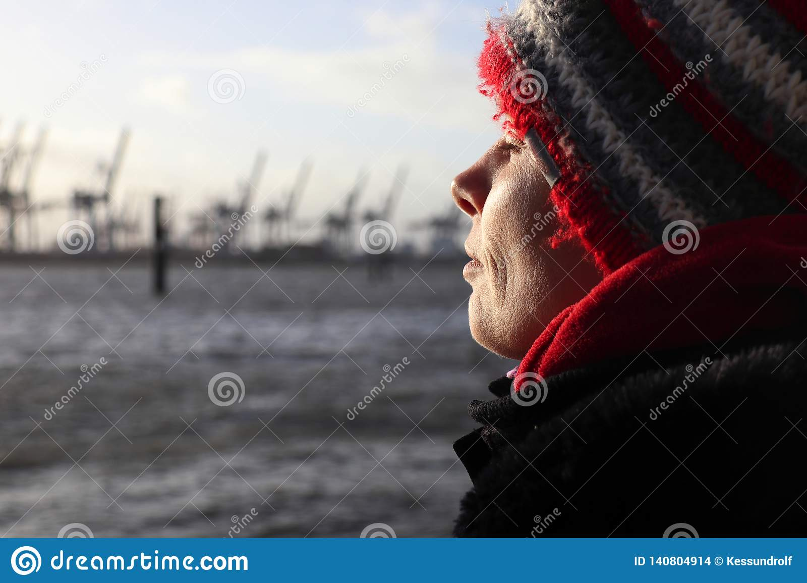 Woman enjoying the sun on a winter day at the river Elbe in Hamburg, Germany