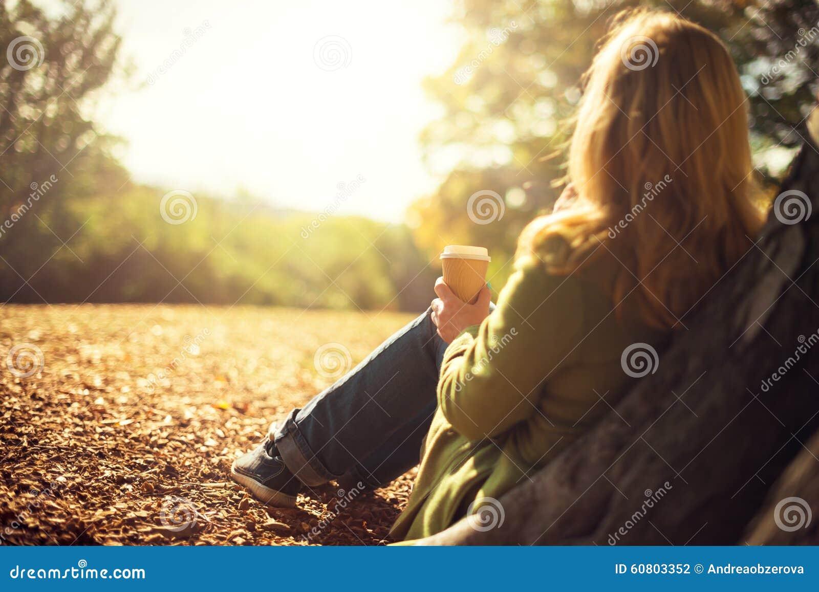 Woman enjoying takeaway coffee cup on sunny cold fall day
