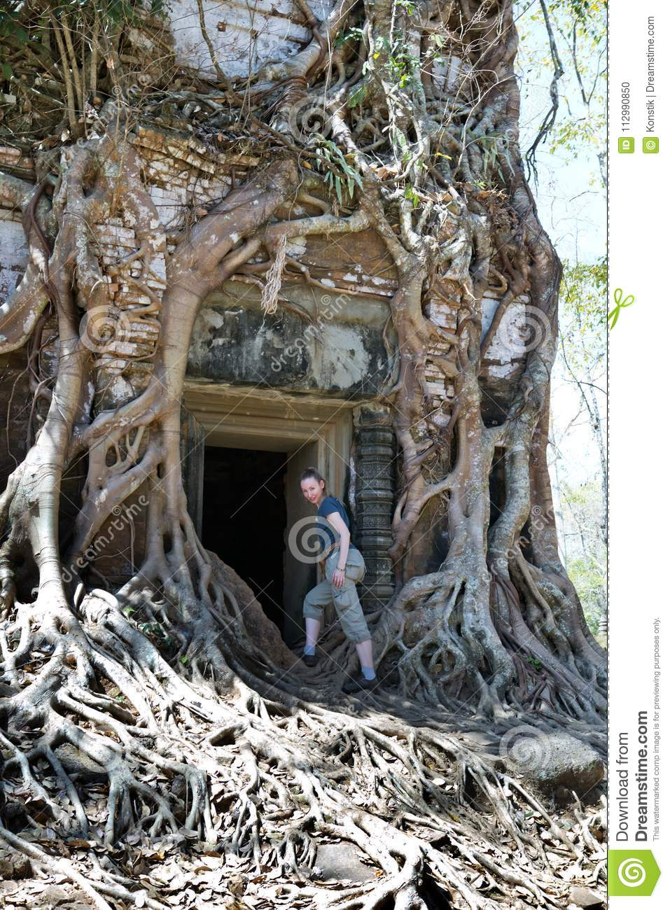 woman at an entrance to the destroyed covered with roots of trees temple Prasat Chrap in the Koh Ker temple complex, Siem Reap, C