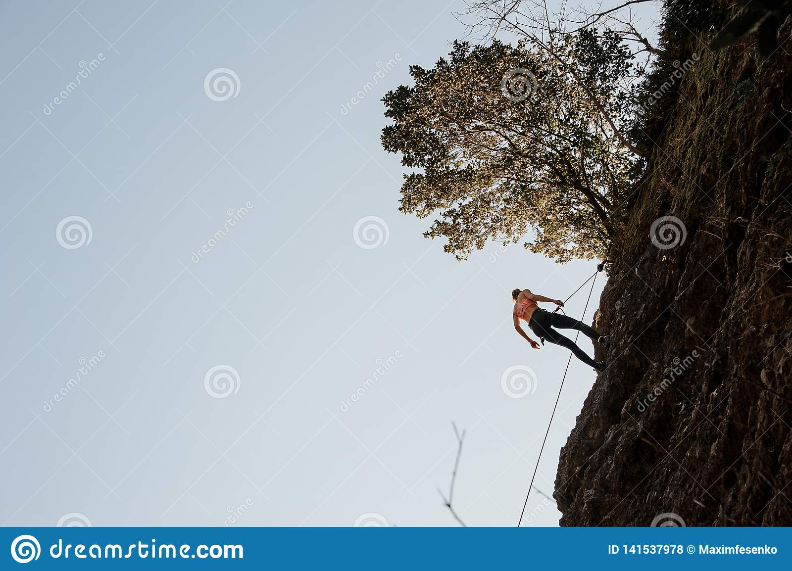 Woman equipped with a rope abseiling on the sloping rock