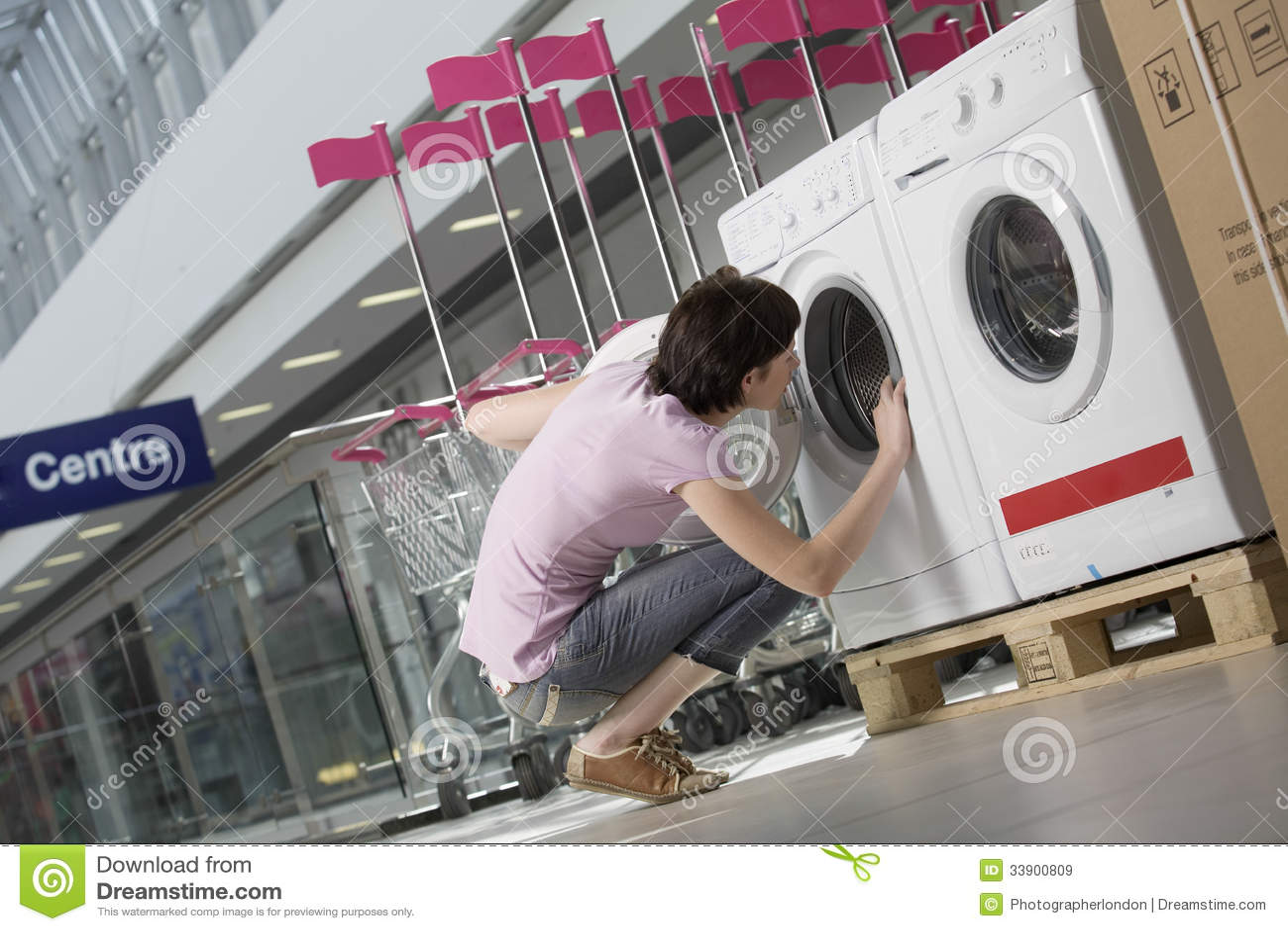 Woman Examining Front Loader Of Washing Machine