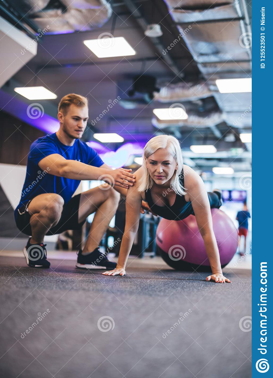 Woman exercising on a ball and a man securing her.