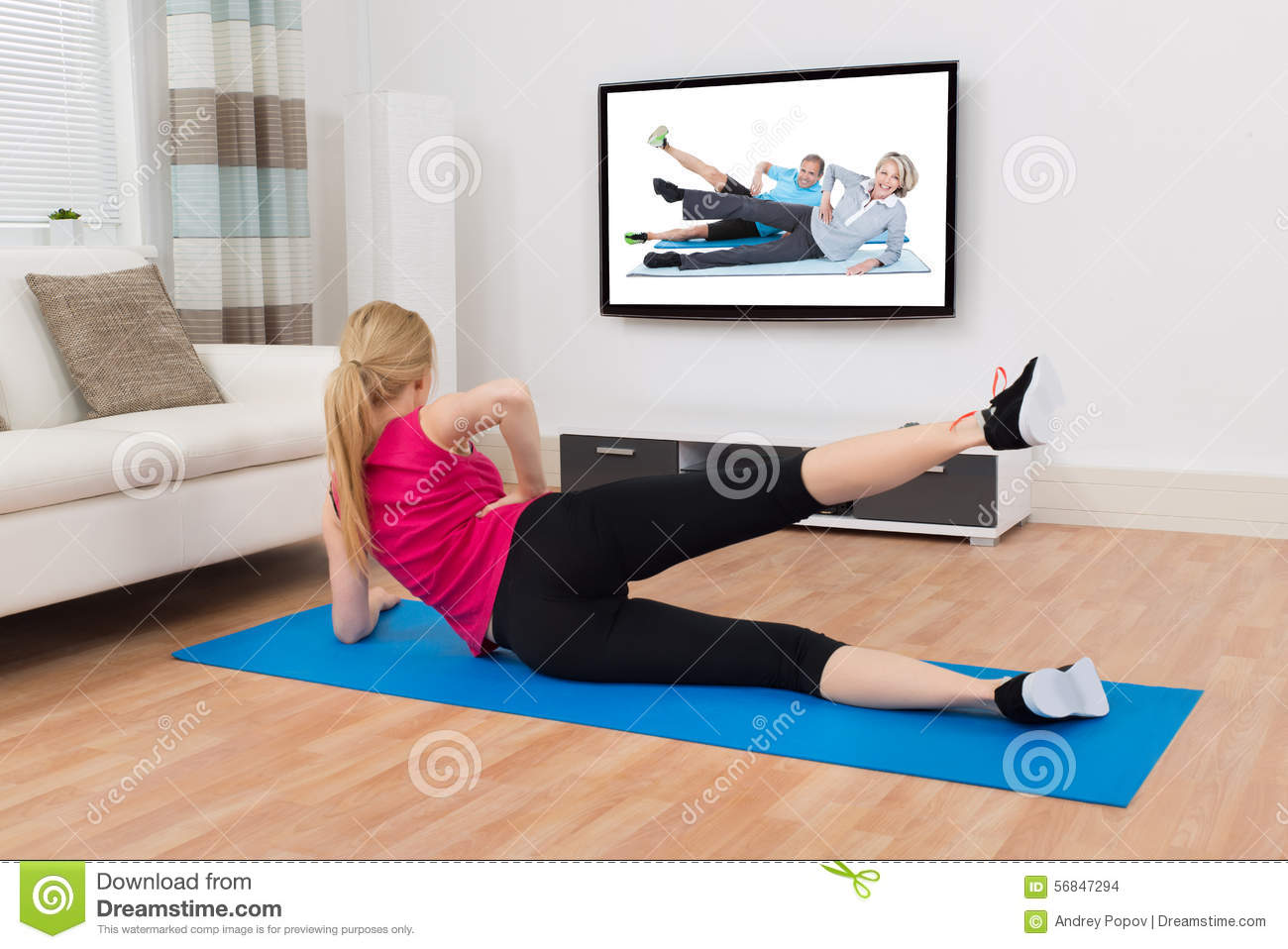 Woman Exercising On Exercise Mat In Front Of Television