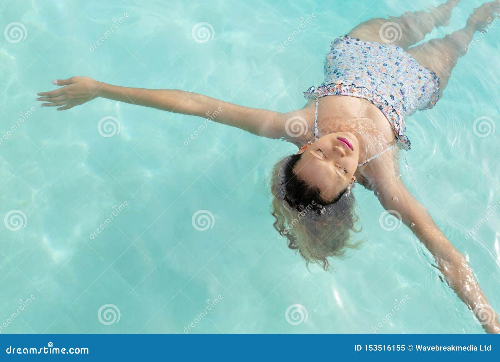 woman eyes closed floating swimming pool backyard home high ange view beautiful caucasian summer fun