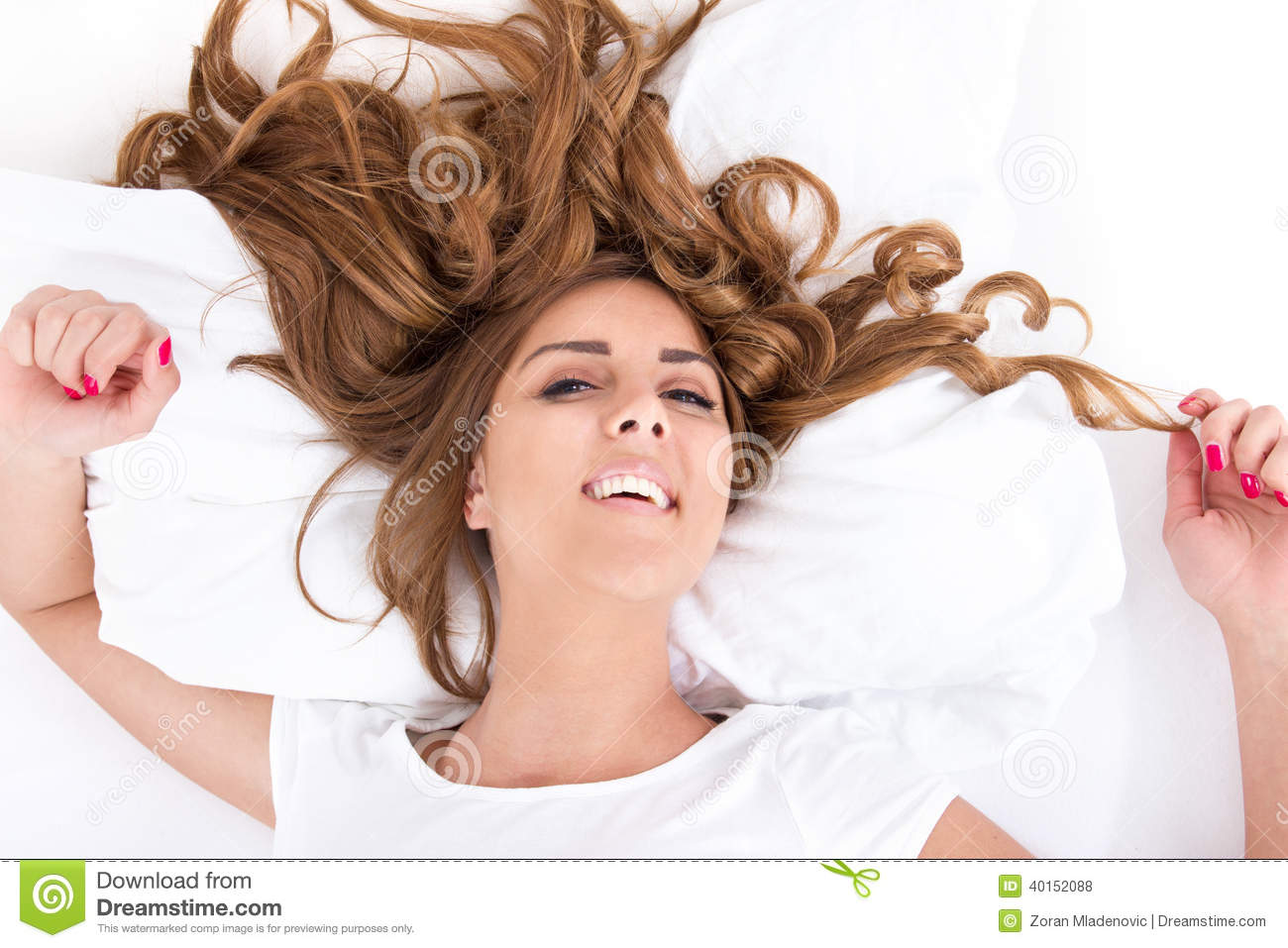 Woman with eyes open and hair spread on bed in bright image