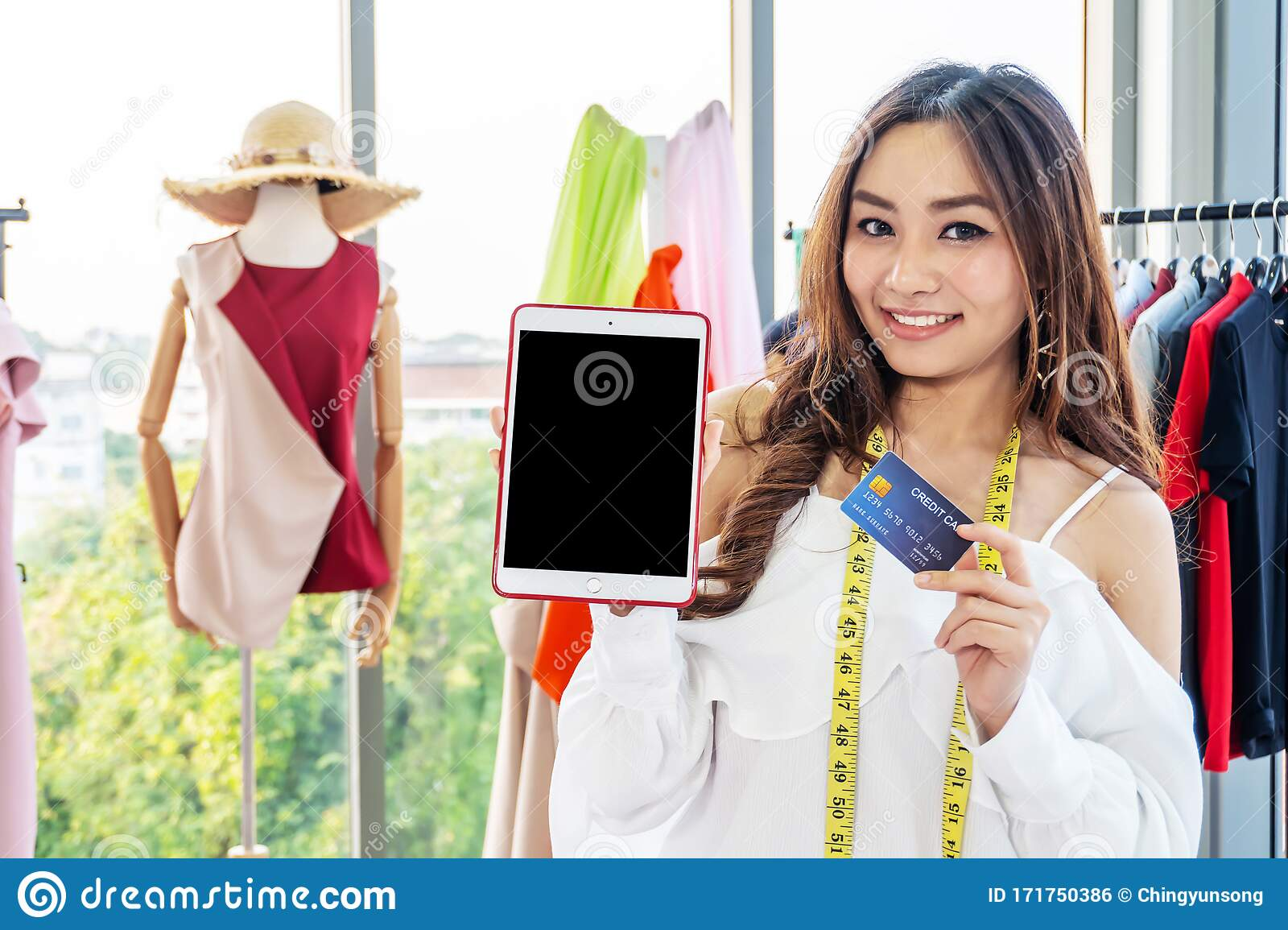Woman Fashion Designer Working In Clothing Shop Studio Is Using Tablet Computer And Holding Credit Card In The Studio Stock Photo Image Of Business Fashion 171750386