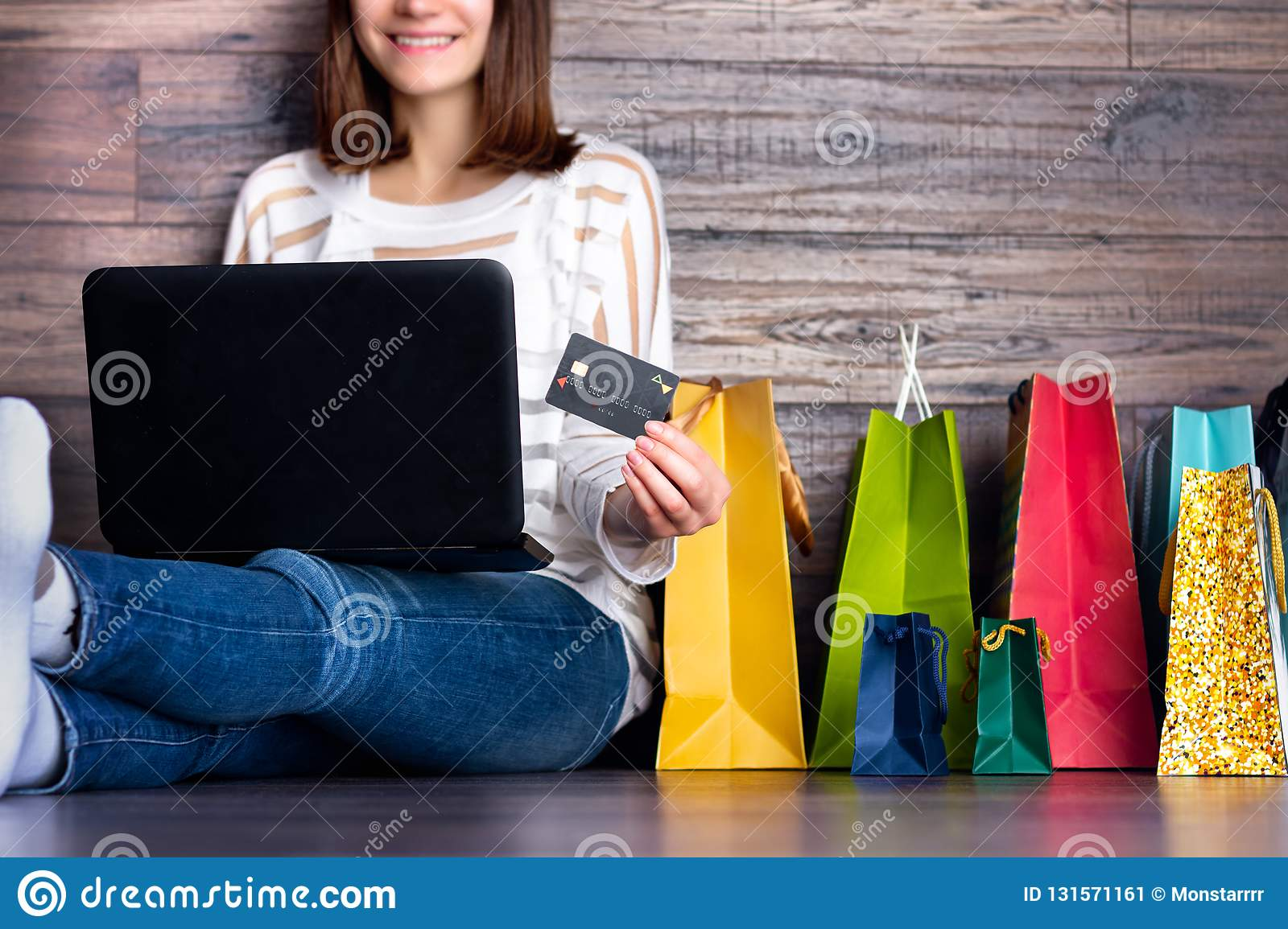 Woman female adult smiling buying making payment on fashion cloth internet online store shop by credit debit card with laptop