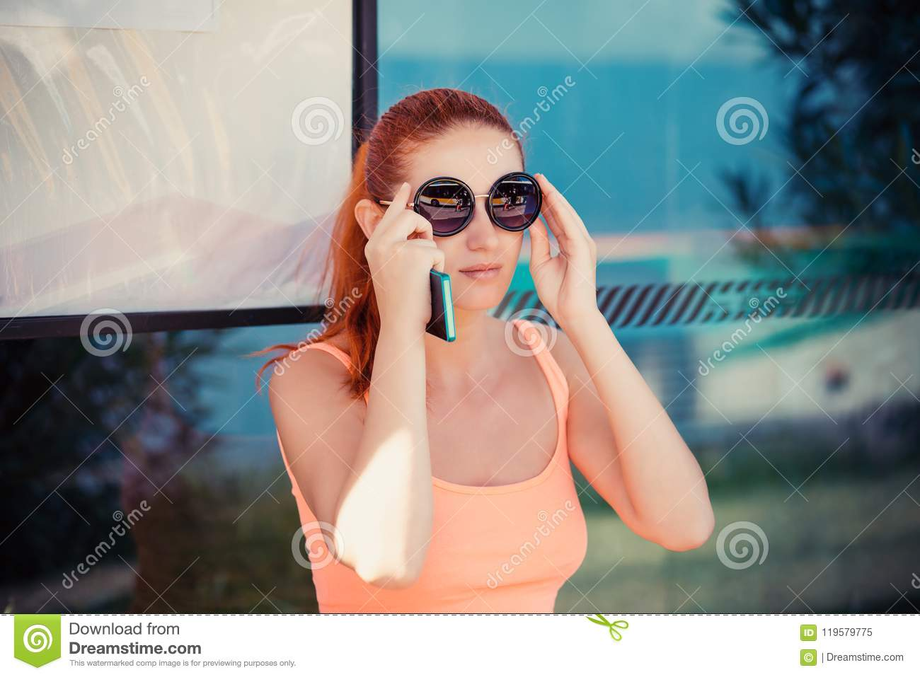 Woman female girl sitting in a bus station adjusting round sunglasses