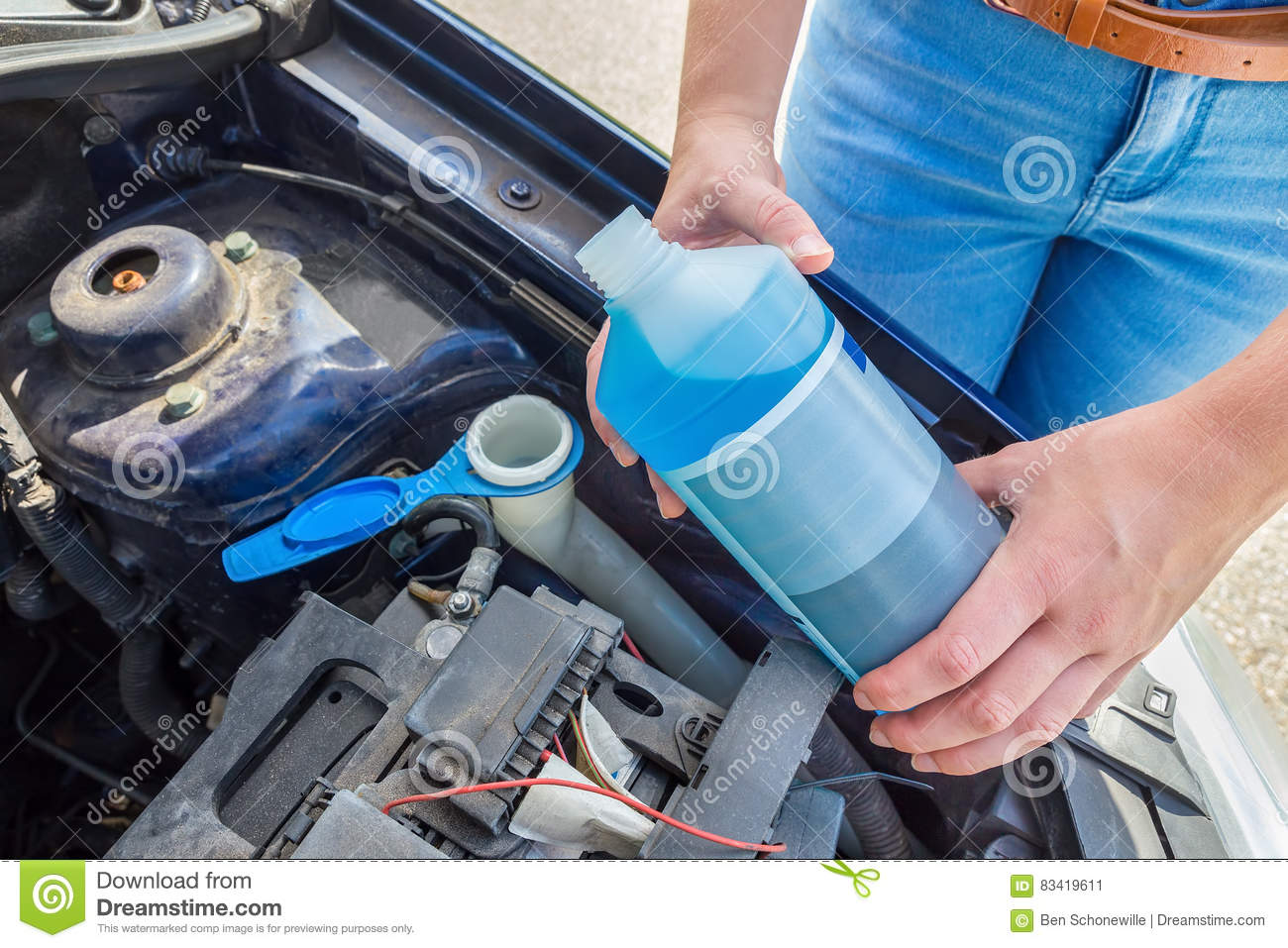 Woman Filling Car Reservoir With Blue Fluid In Bottle