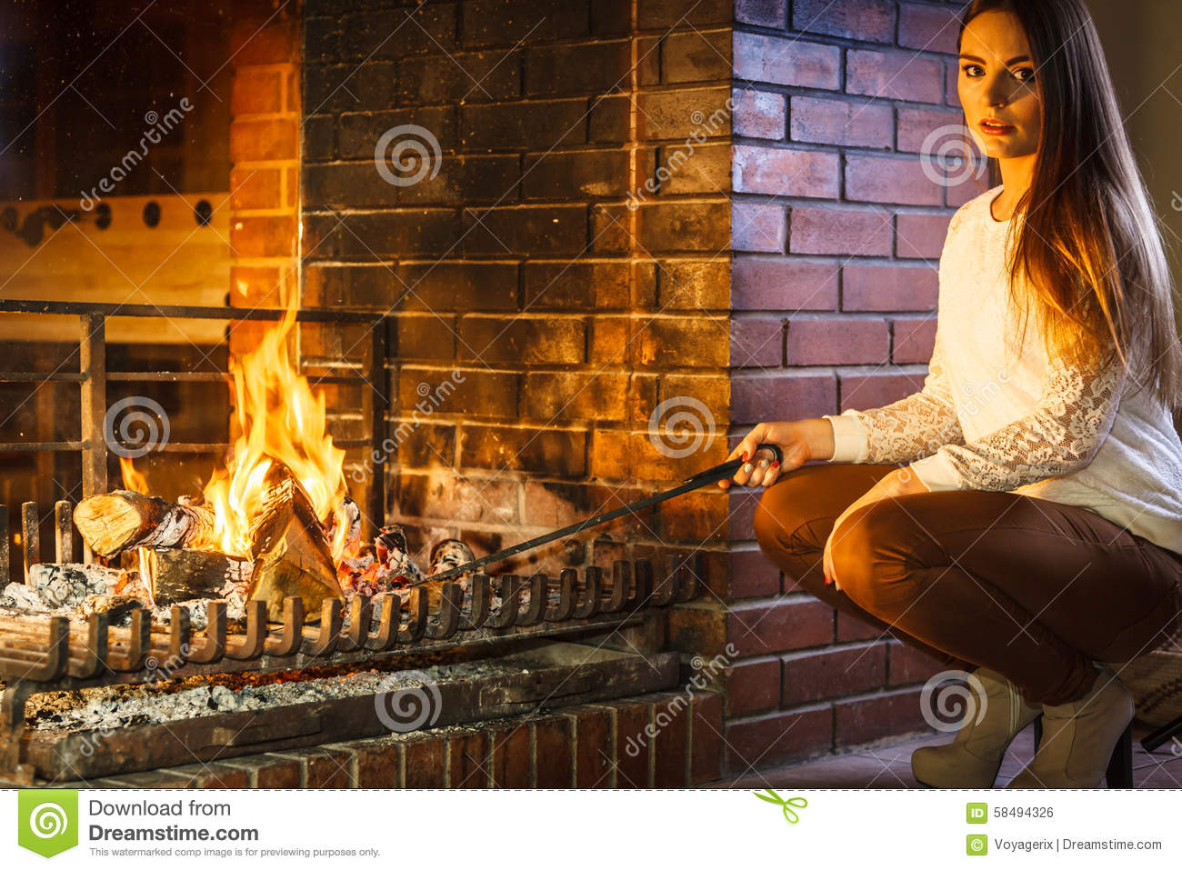 woman with fire iron poker at home fireplace stock photo image