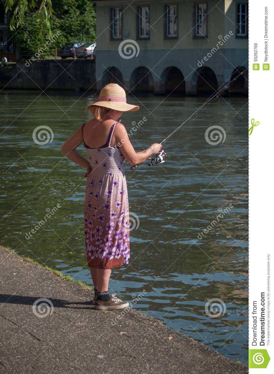 woman with Fishing rod on IL river at little France quarter in Strasbourg