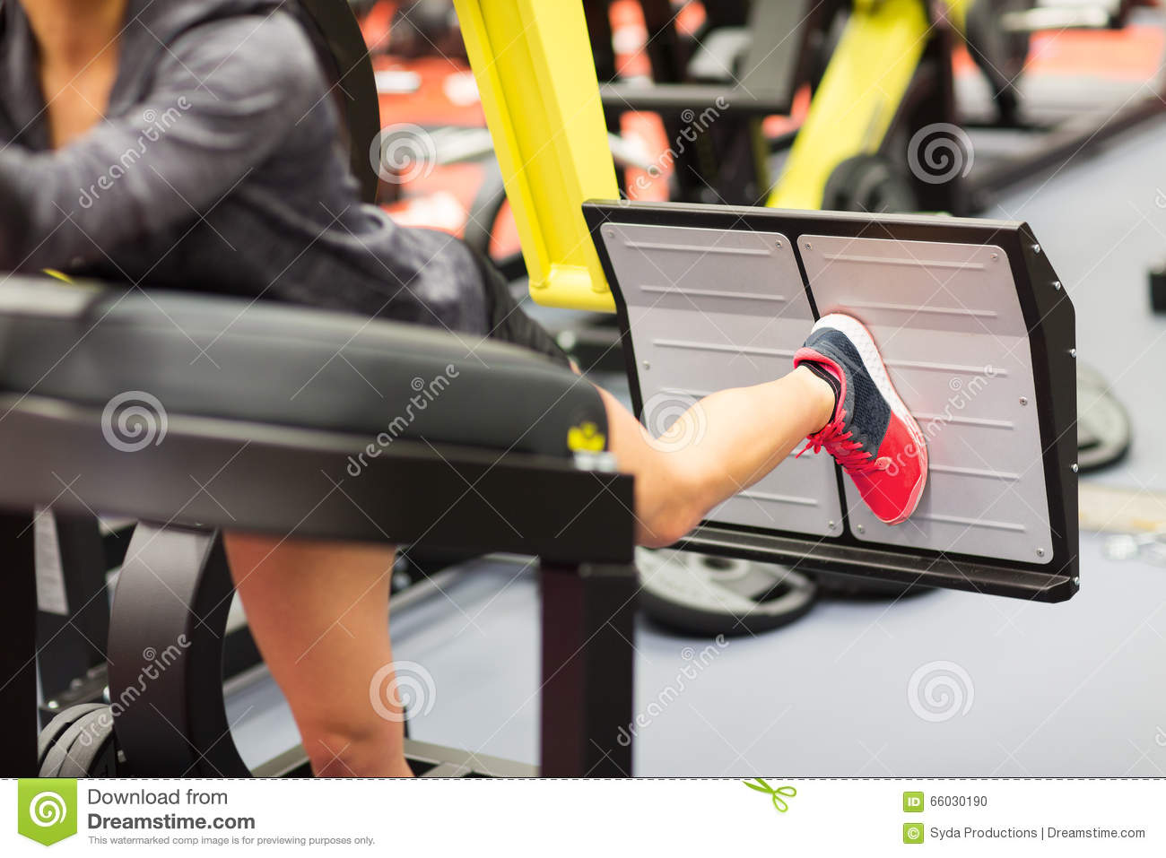 Woman Flexing Muscles On Leg Press Machine In Gym Stock Photo