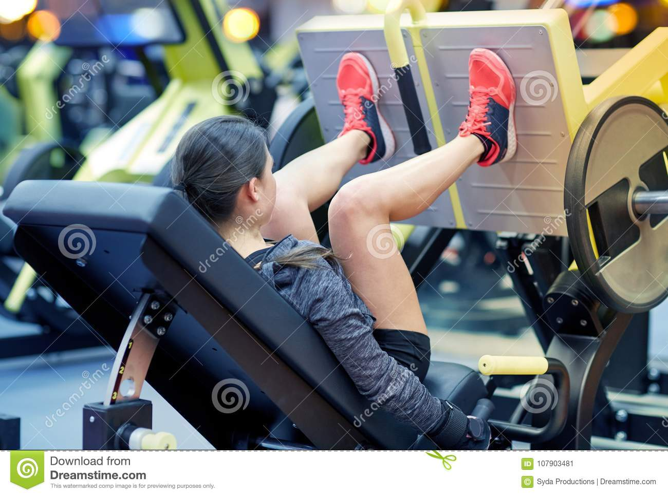 Woman Flexing Muscles On Leg Press Machine In Gym Stock Image