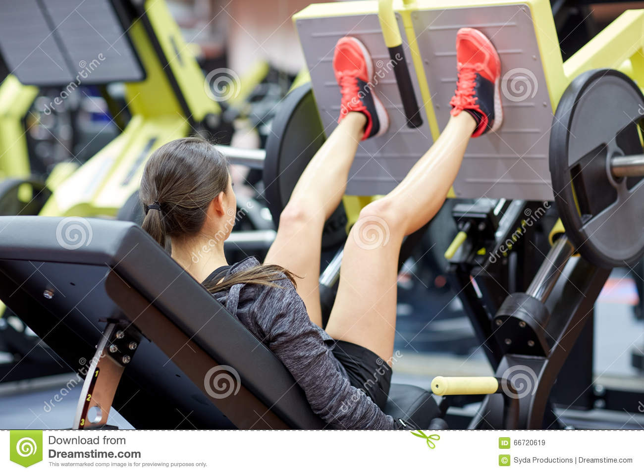 Woman flexing muscles on leg press machine in gym stock for Gimnasio yong