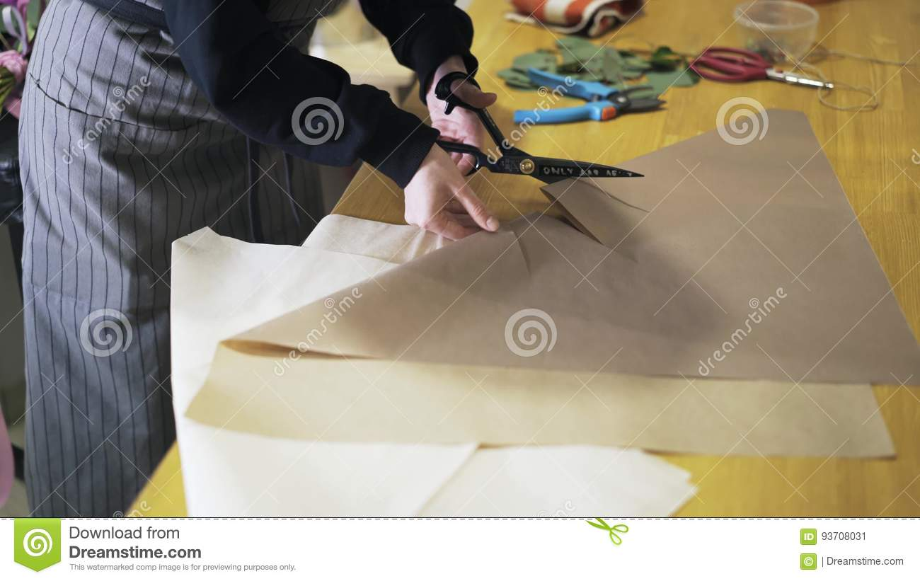 Woman Florist Folding And Cutting Paper On Desk To Wrap Flowers