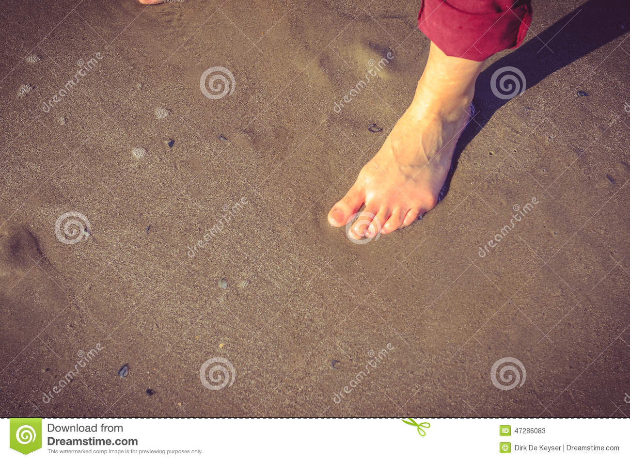Woman foot on wet sand