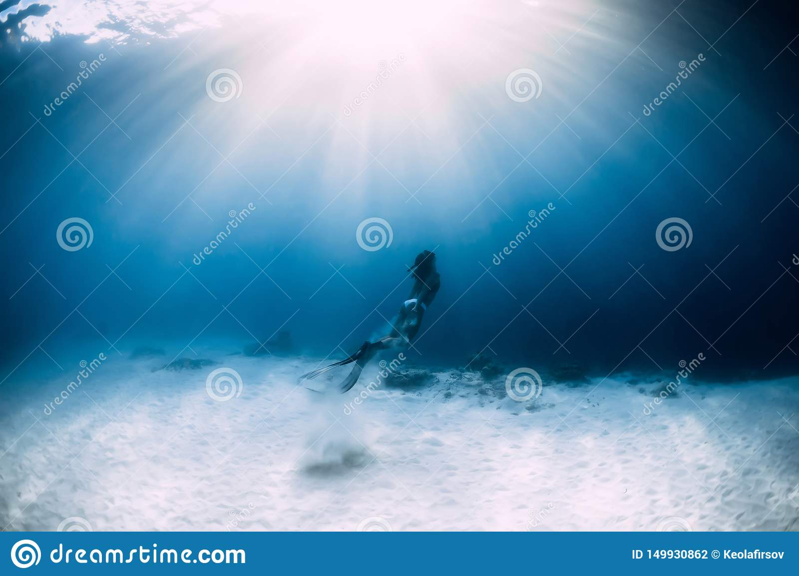 Woman freediver in bikini over sandy sea with fins. Freediving underwater