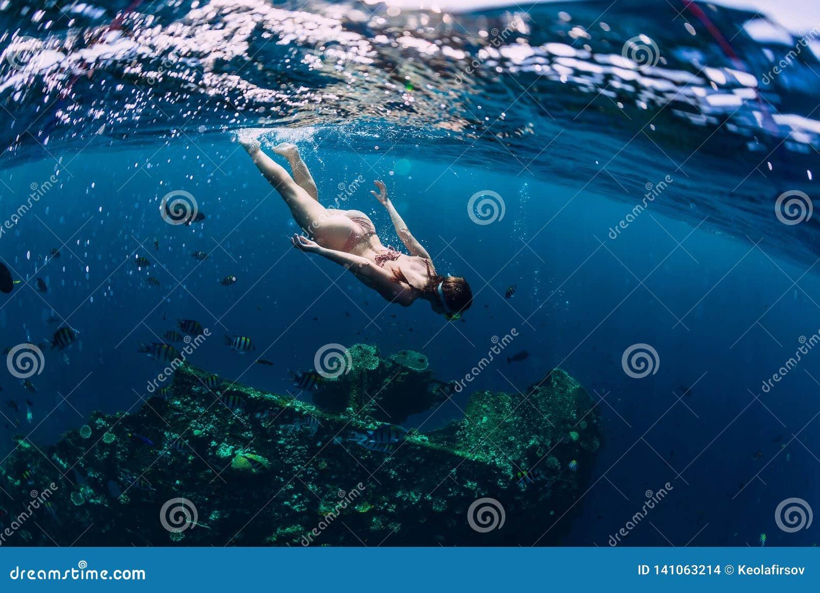 Woman freediver in bikini swin in tropical ocean at shipwreck