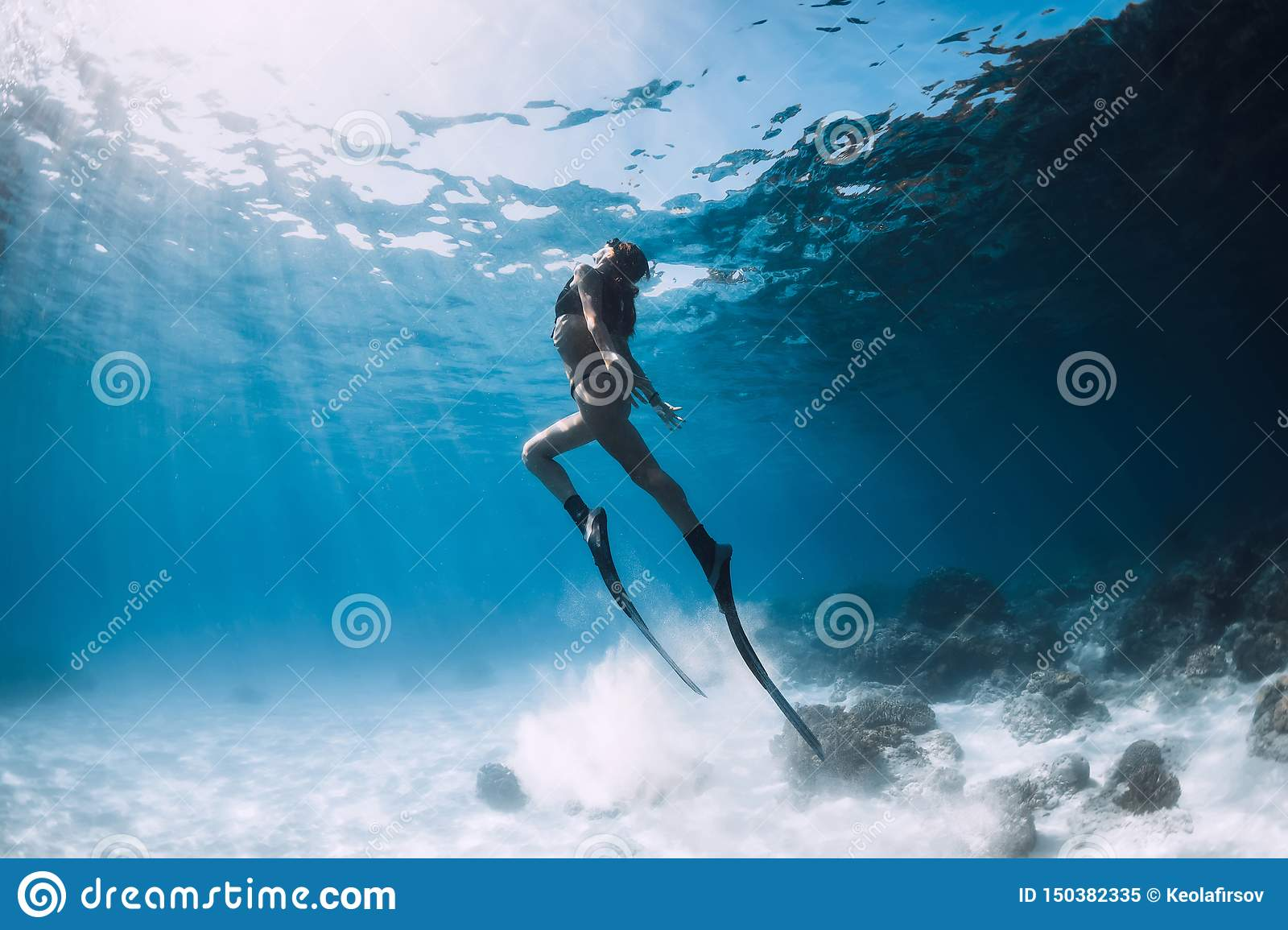 Woman freediver glides over sandy sea with fins.