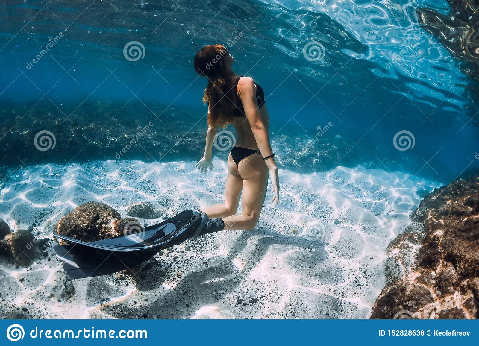Woman freediver glides over sandy sea with fins
