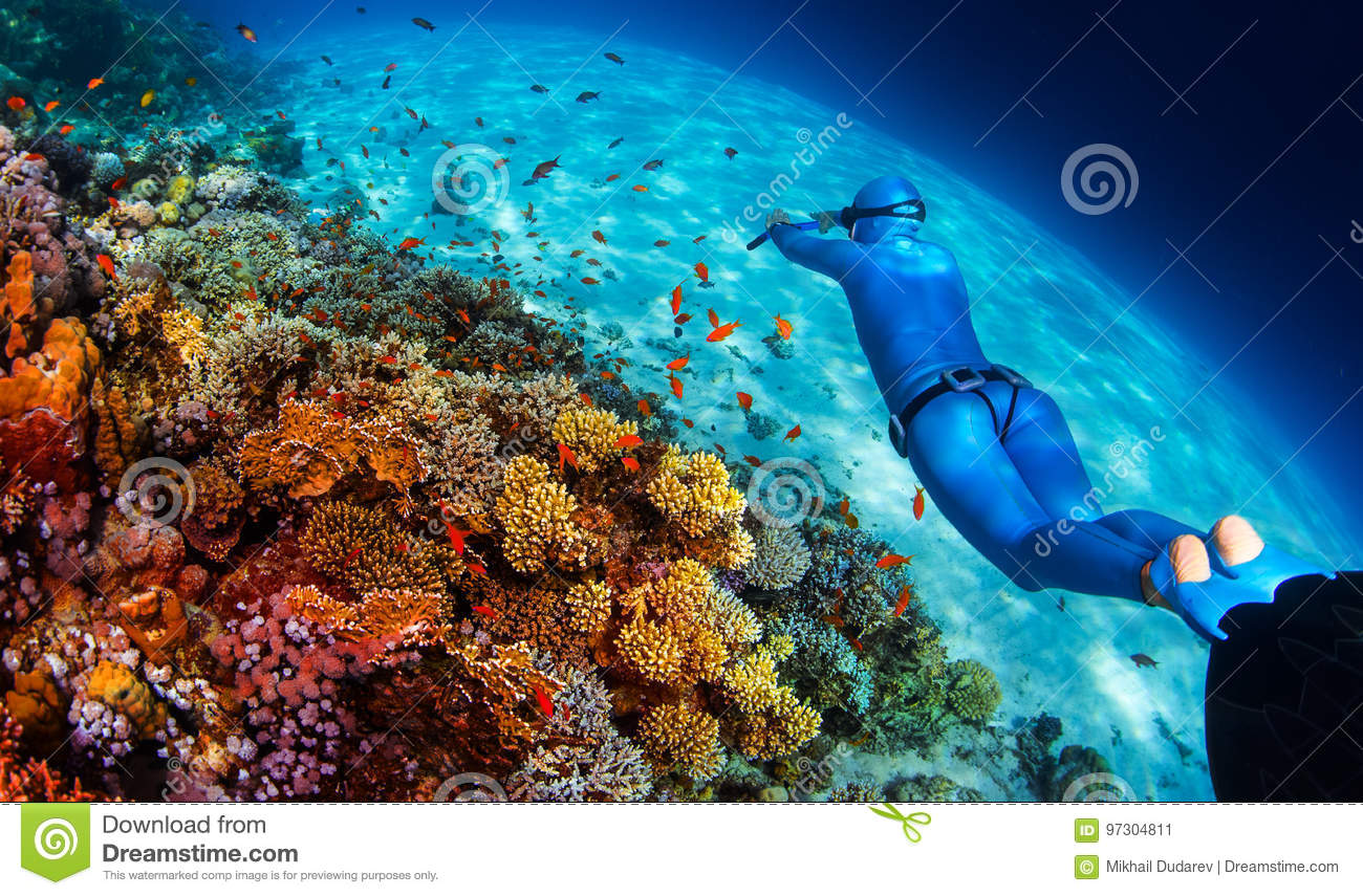 Woman freediver glides over vivid coral reef