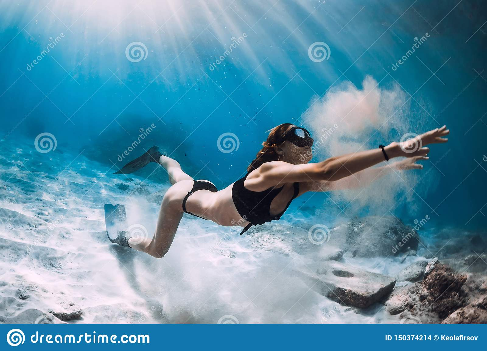 Woman freediver with sand over sandy sea with fins. Freediving in Hawaiian island