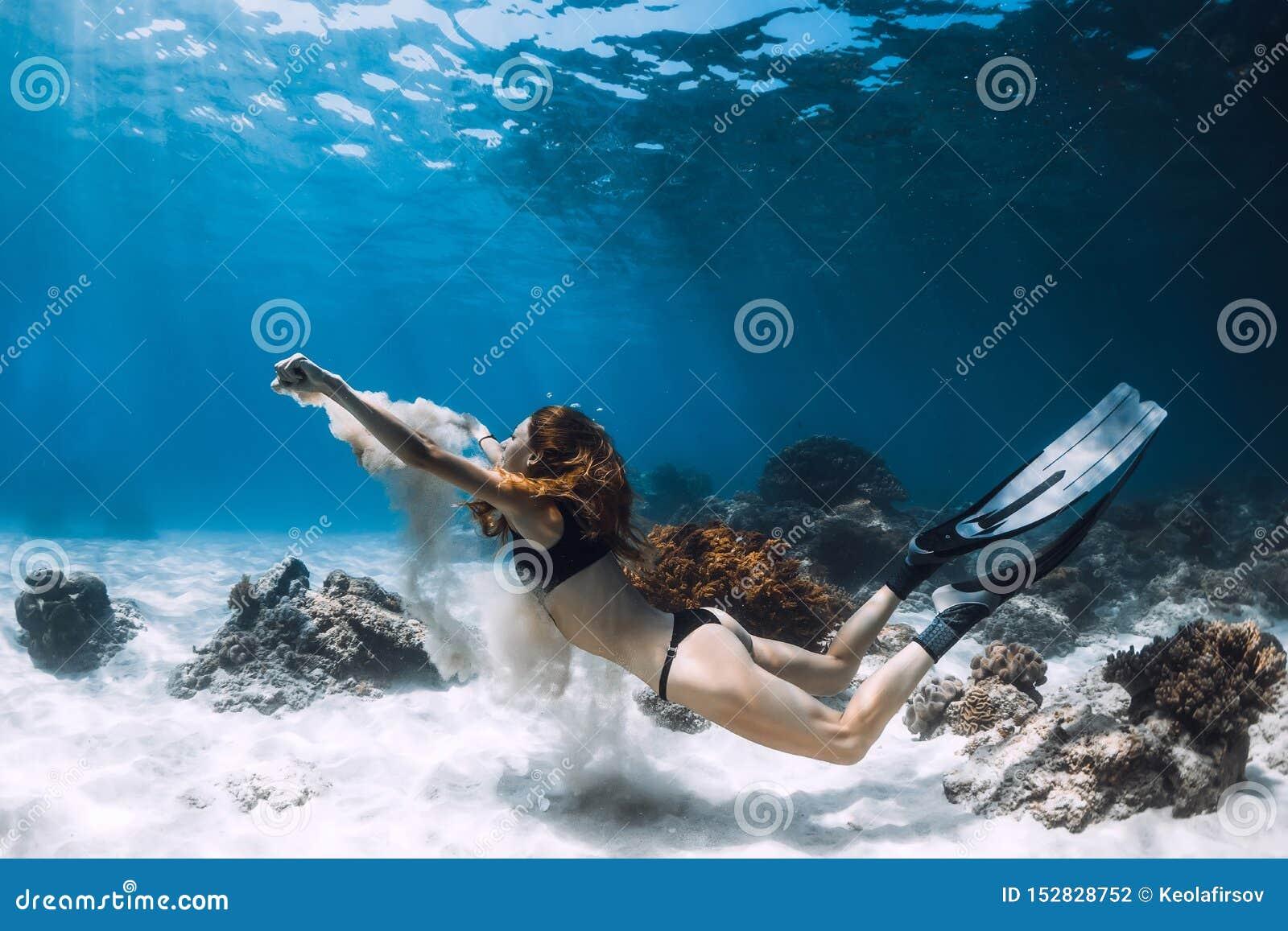 Woman freediver swim underwater over sandy bottom with sand