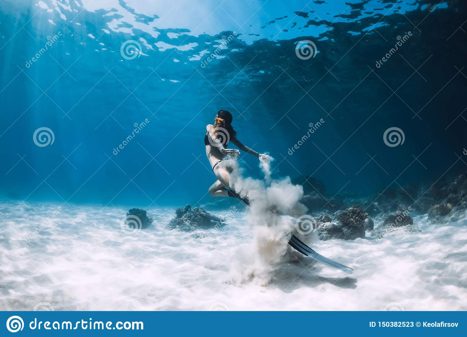 Woman freediver with white sand glides over sandy sea with fins. Freediving underwater