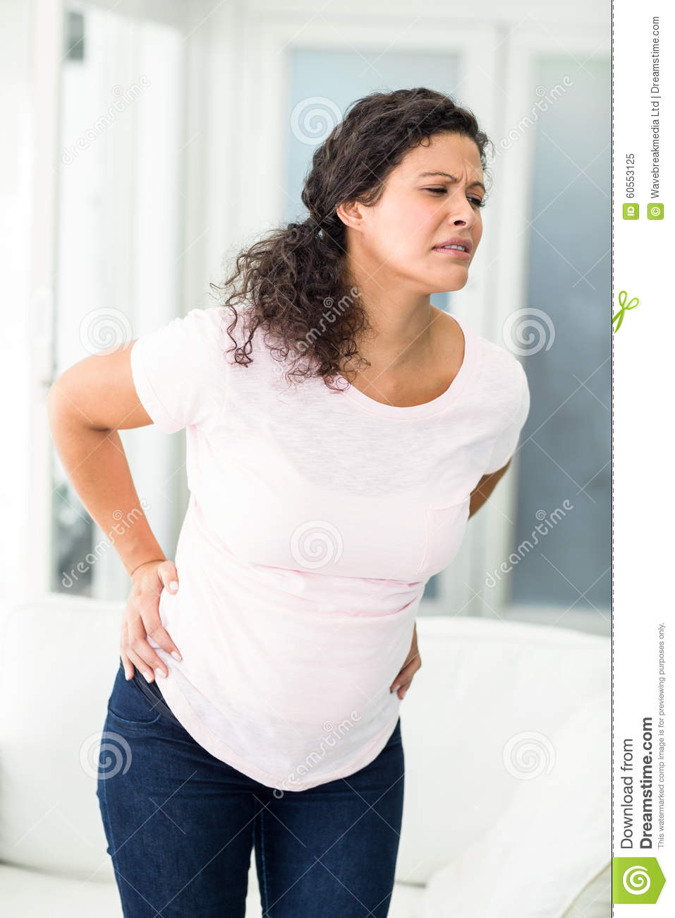 Pregnant woman frowning in back pain standing in living room.