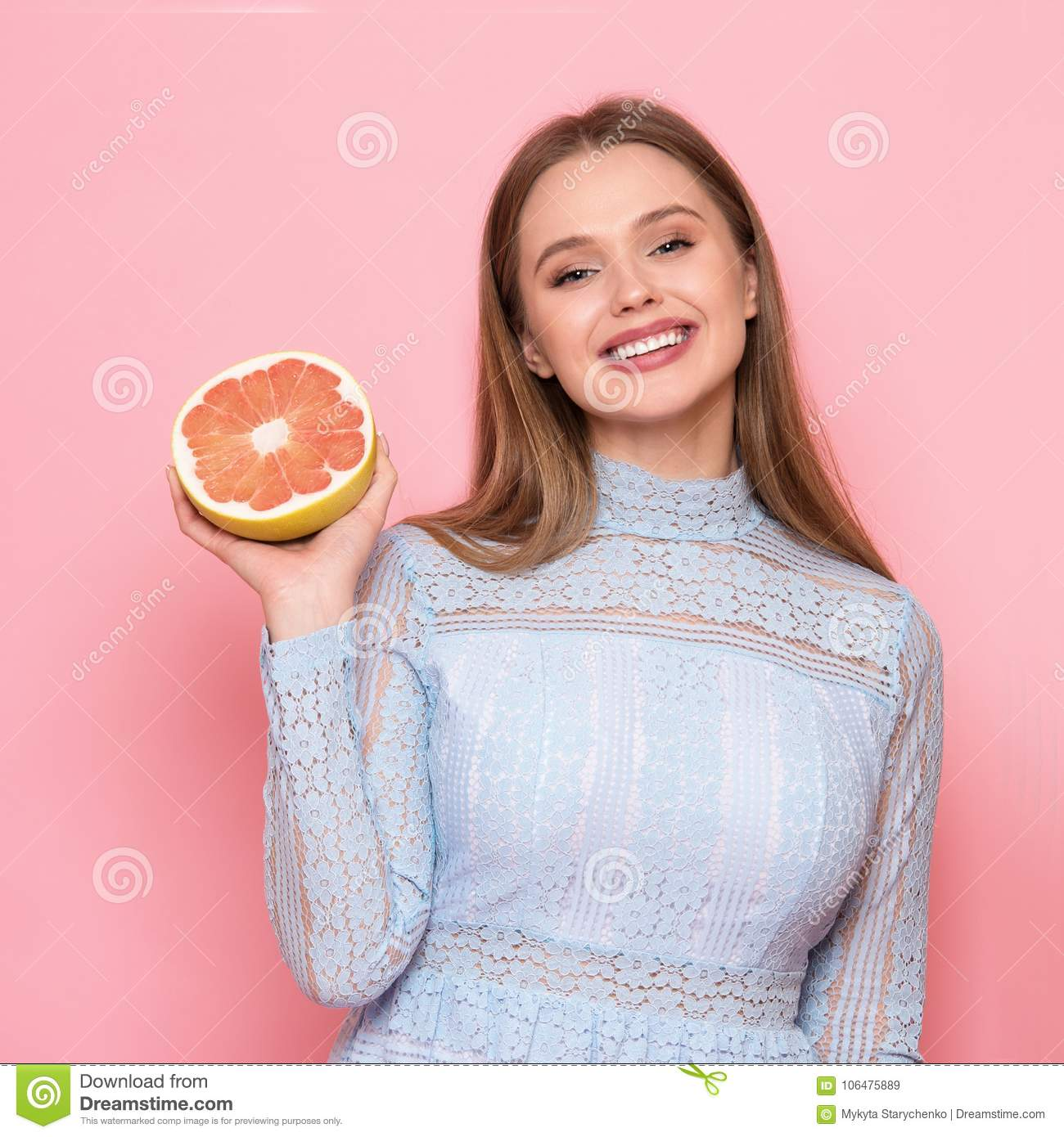 Woman fruit diet and healthy food eating concept. Girl holds grapefruit in hands.