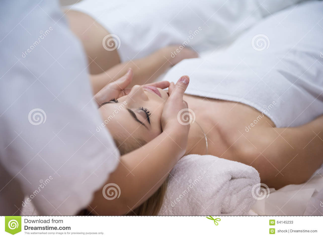 Woman getting face and head massage in spa salon