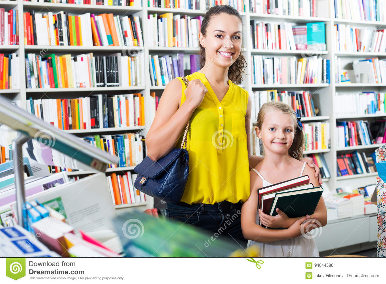 Woman With Girl Buying Books