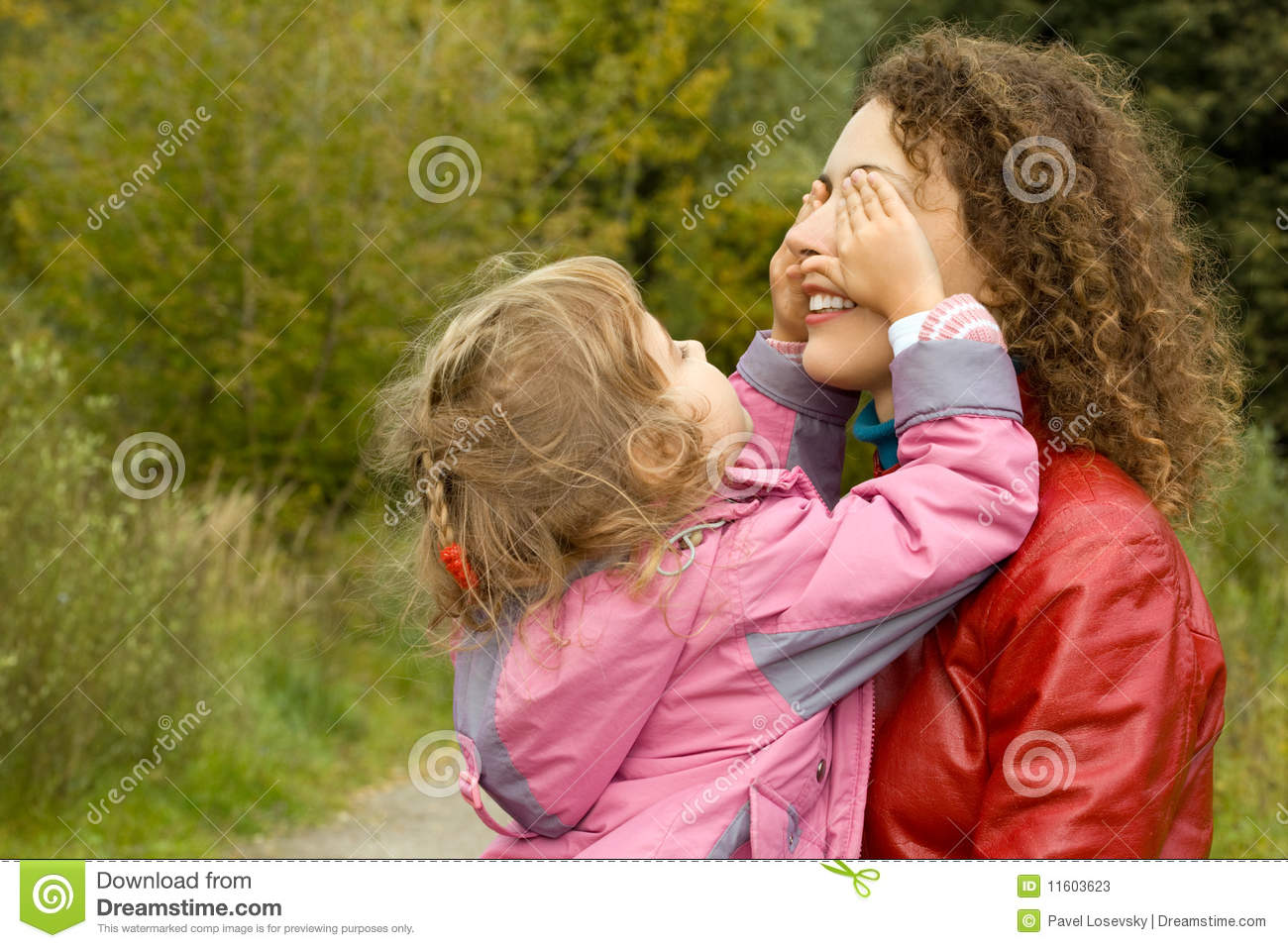 Woman and girl playing in garden, girl closes eyes