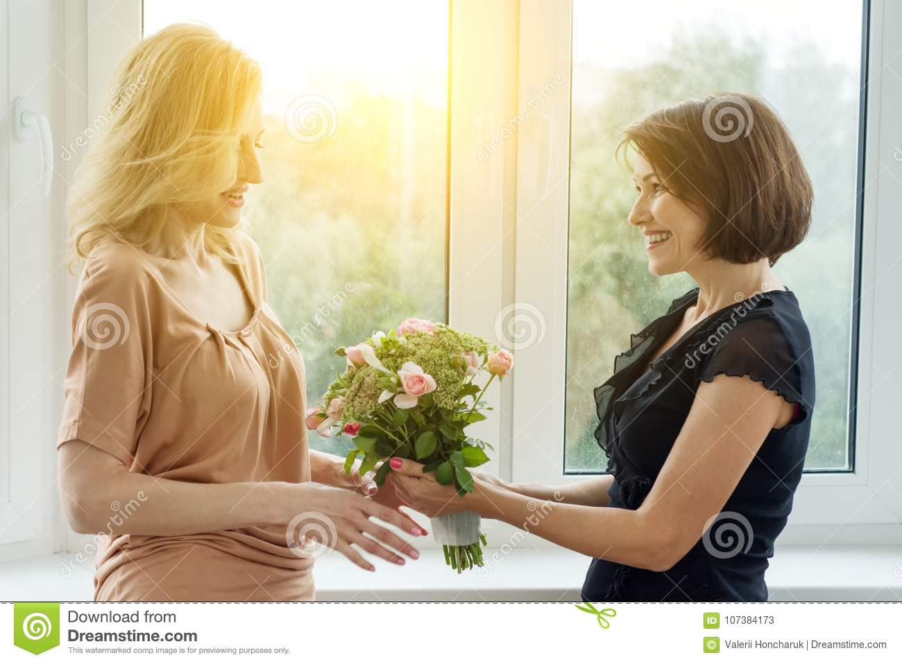 Woman Giving Bouquet Of Beautiful Flowers To Her Girlfriend Woman