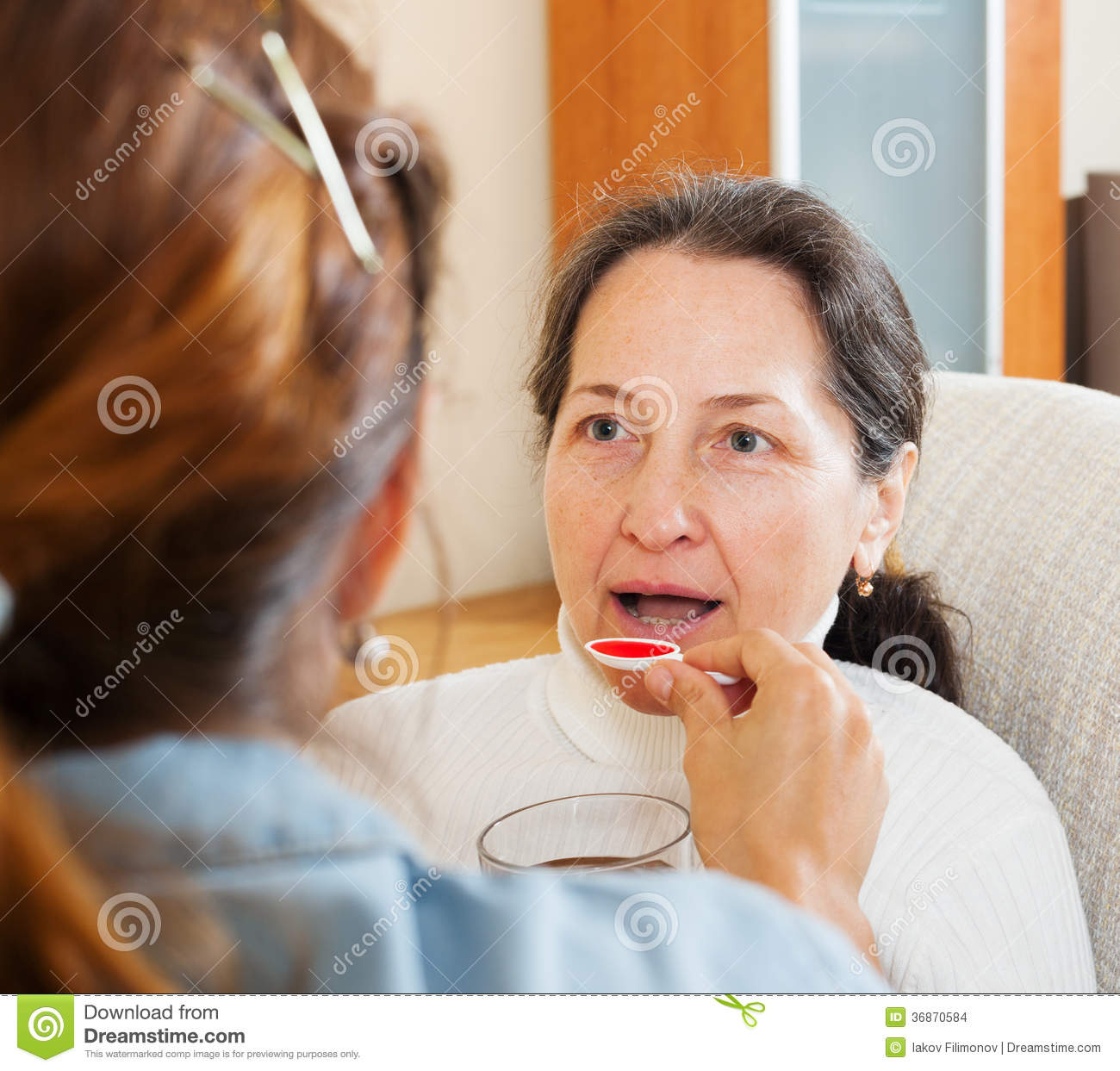 Woman Giving The Cough Syrup To Mother Stock Photo ...