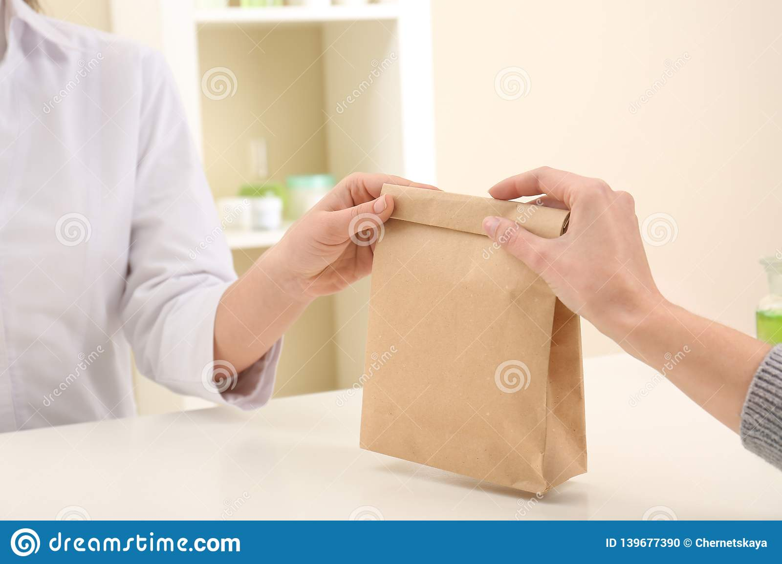 Woman giving paper bag with order to customer in shop, closeup.