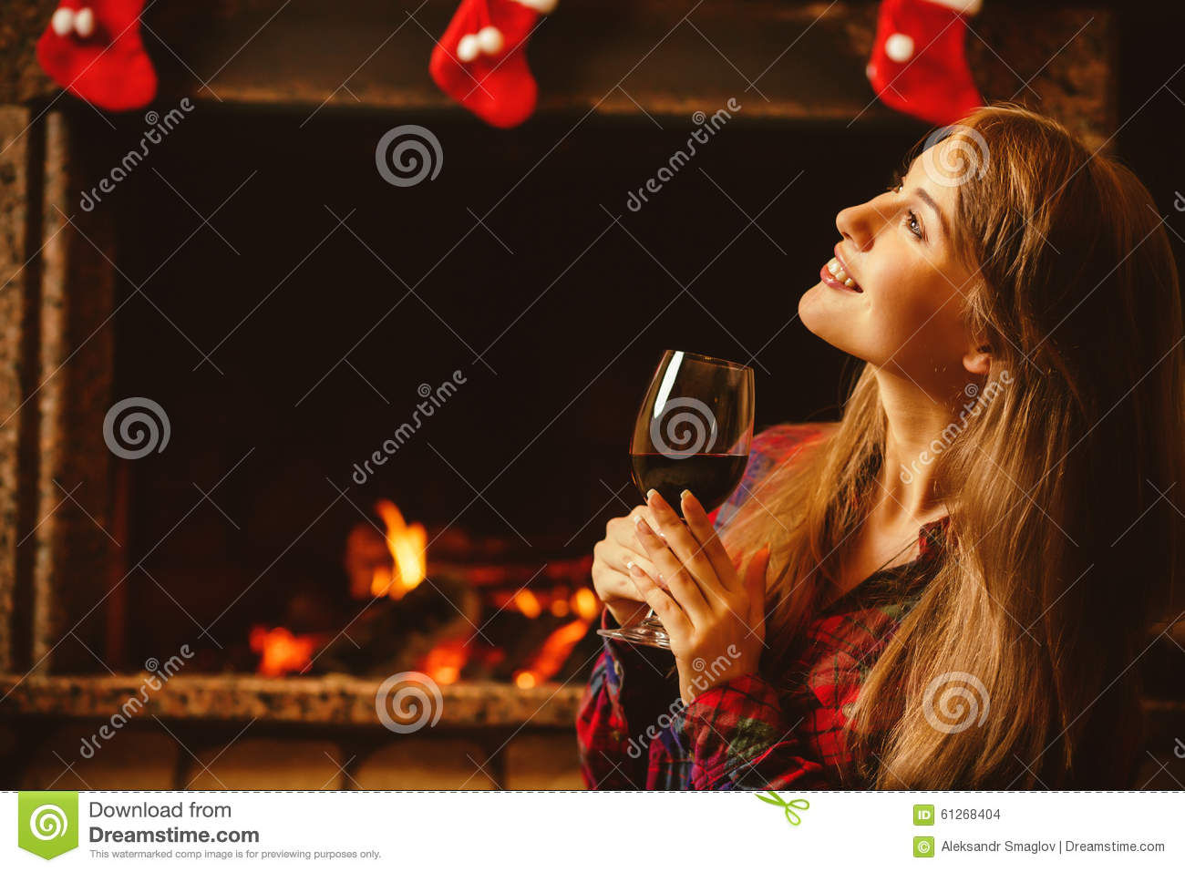 Woman with a glass of wine by the fireplace. Young attractive wo
