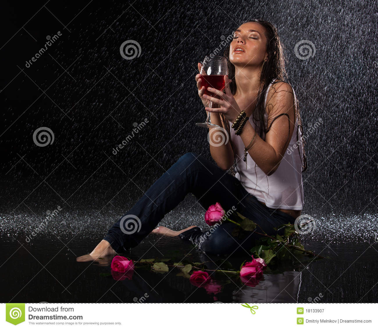 Woman with and glass of wine under rain.