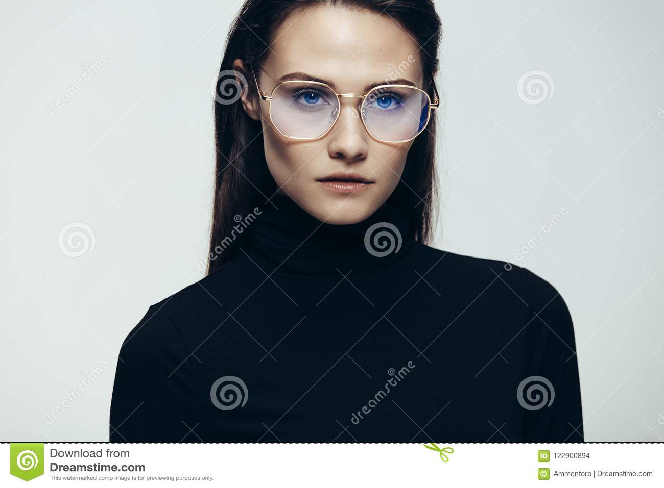 68dae78fbcd Close up portrait of woman wearing glasses staring with an intense  expression. Female model in black dress on grey background.