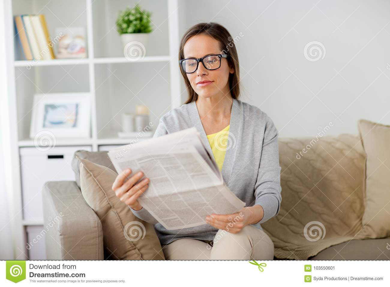 woman in glasses reading newspaper at home stock image - image of