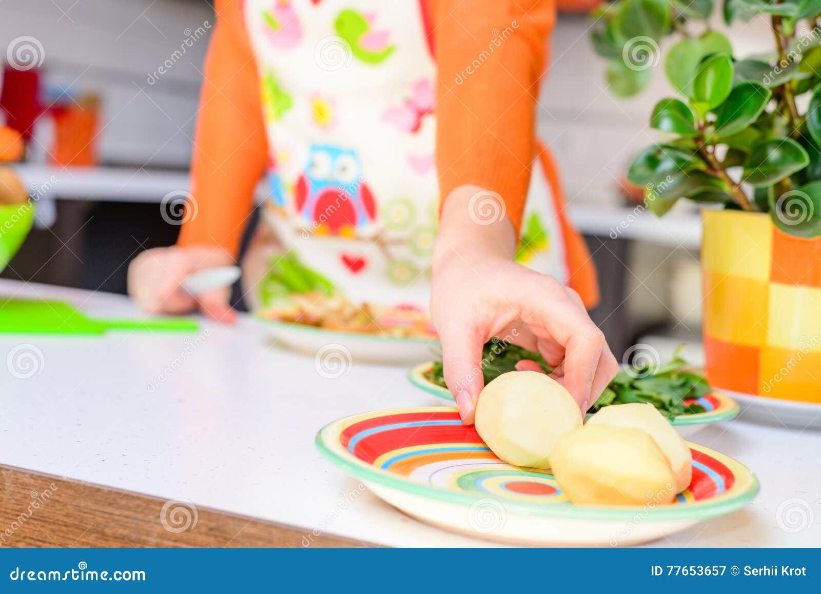 Woman grab peeled potato by hand,in modern kitchen