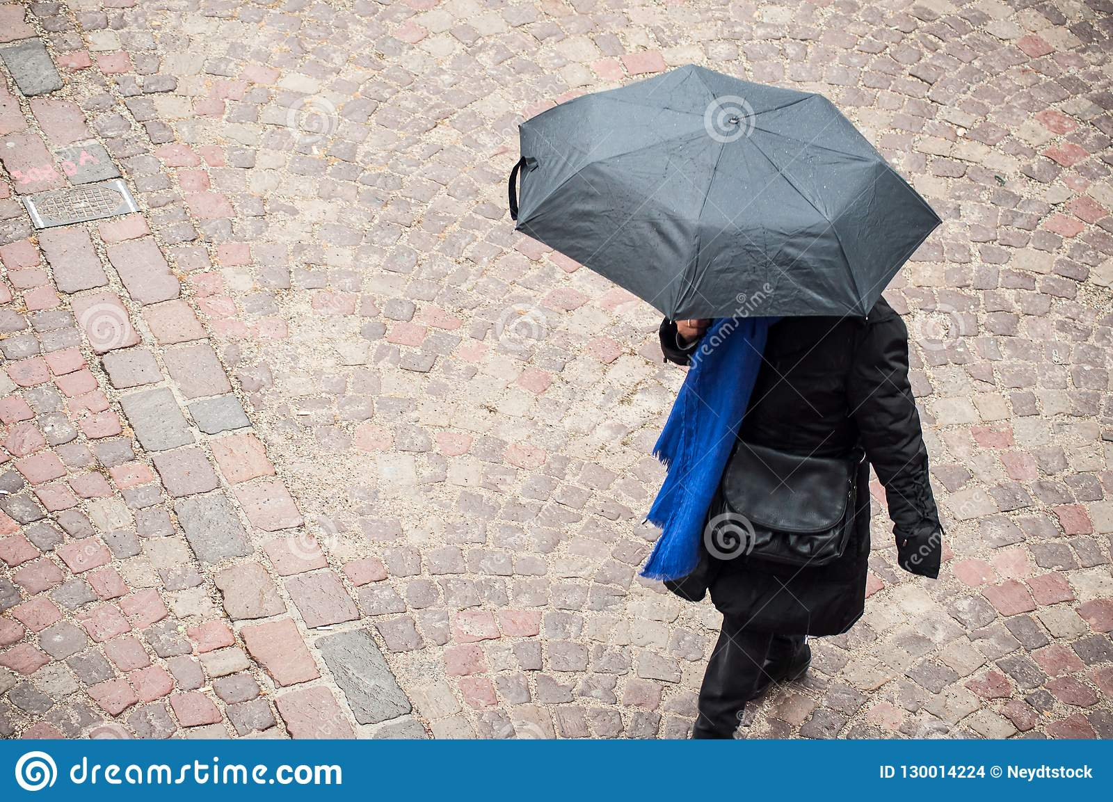 Woman with grey umbrella on cobbles place in the ci