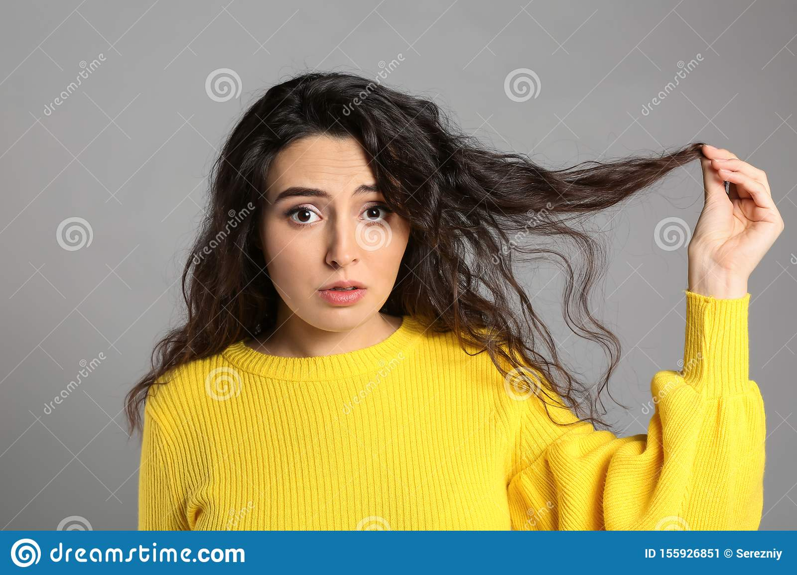 Woman with hair loss problem on grey background